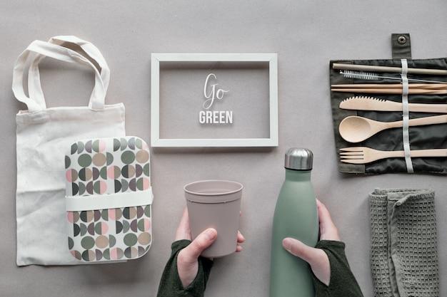 """Kreatywny widok z góry, zero marnowanych paczek koncepcji lunchu. zestaw obiadowy na wynos leżący na płasko - bambusowe sztućce, pudełko, bawełniana torba i ręka z filiżanką na wynos na brązowym papierze. ramka z tekstem """"go green""""."""