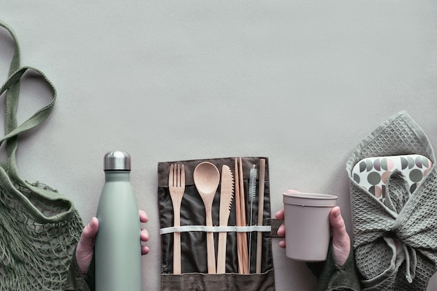 Kreatywny widok z góry, zero pakowanych opakowań na lunch, zestaw pudełek na wynos z bambusowymi sztućcami, pudełko wielokrotnego użytku, bawełniana torba i ręka z filiżanką kawy na wynos powyżej na brązowym papierze. zrównoważony styl życia.