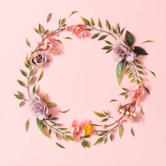 Kreatywny wiosenny układ wykonany z kolorowych kwiatów i zielonych liści na pastelowo różowej powierzchni