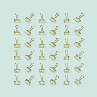 Kreatywny wzór kartki okolicznościowej z materiałami biurowymi, złote metalowe spinacze do papieru.