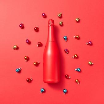 Kreatywny wzór z czerwonej malowanej makiety butelki na czerwonym tle pokryte kolorowe szklane kulki noworoczne z miejsca na kopię. kartkę z życzeniami świątecznymi.