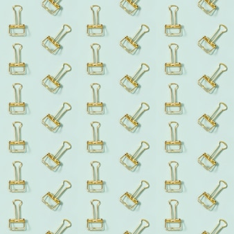 Kreatywny wzór z materiałów biurowych, złote metalowe spinacze do papieru.