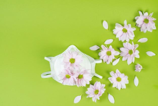 Kreatywny wzór z medyczną maską ochronną przed chorobami, koronawirusem i wiosennymi kwiatami