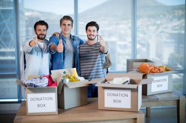 Kreatywny zespół biznesowy stojący w pobliżu pudełka z darowiznami i pokazujący kciuki do góry w biurze