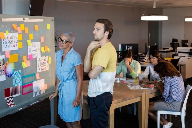 Kreatywnych ludzi biznesu patrząc na karteczki na szklanej desce w biurze