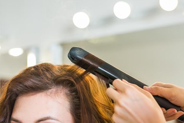 Kręcenie włosów w salonie kosmetycznym. profesjonalny salon fryzjerski stylizacja włosów kręconych długich kobiet.