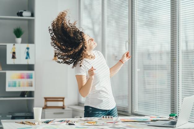 Kręcona artystka tańcząca przy stole ze sprzętem artystycznym