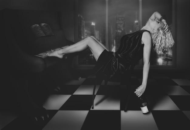 Kręcona blondynka siedzi przy pianinie z winem