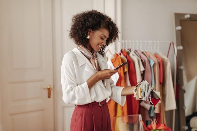 Kręcona ciemnoskóra urocza dama w bordowych spodniach i białej bluzce uśmiecha się, trzyma telefon i robi zdjęcie próbek tekstyliów
