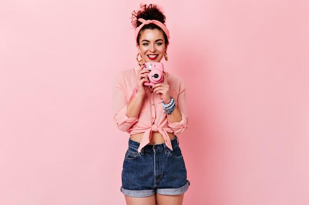 Kręcona dama w różowej bluzce i dżinsowych szortach uśmiecha się i trzyma mini aparat na odosobnionej przestrzeni.