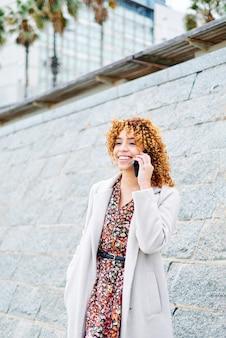 Kręcona dziewczyna afro rozmawia przez telefon
