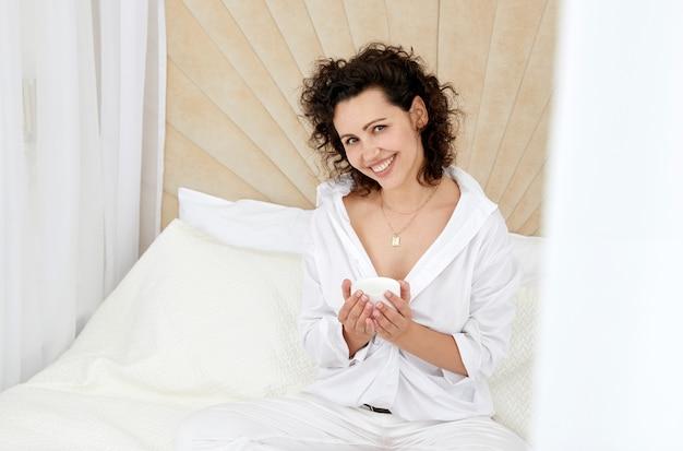 Kręcona dziewczyna siedzi na białym łóżku trzymając filiżankę kawy
