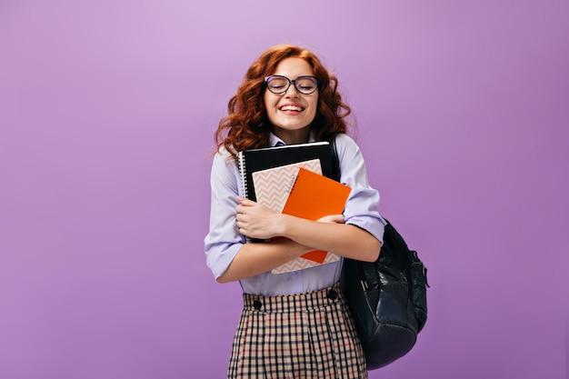 Kręcona dziewczyna w okularach trzyma zeszyty na fioletowej ścianie