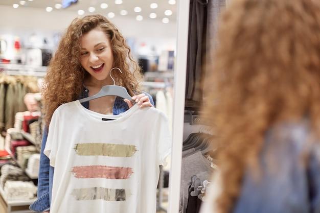 Kręcona dziewczyna z szerokim uśmiechem wybiera koszulkę przed dużym lustrem sklepowym. te ubrania białe w paski w środku trzech kolorów