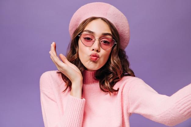 Kręcona fajna dziewczyna posyła buziaka i robi selfie na fioletowej ścianie