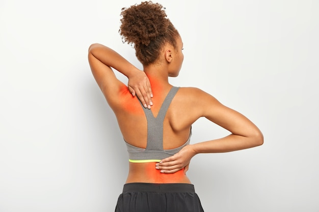 Kręcona kobieta bez twarzy cierpi na bóle kręgosłupa, nosi sportowy stanik, pokazuje lokalizację zapalenia, na białym tle.