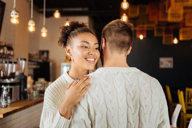 Kręcona kobieta. ciemnowłosa kobieta z kręconymi włosami w ładnych, jasnych kolczykach przytulająca swojego chłopaka na spotkanie z nim