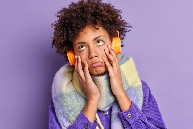 Kręcona kobieta czuje się znudzona, gdy słucha monotonnej piosenki, której niezadowolony jest tępy, niezainteresowany wyraz twarzy, nosi słuchawki stereo na uszach, nosi modne zimowe ubrania. styl życia ludzi