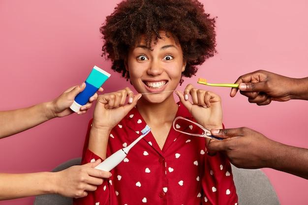 Kręcona kobieta dba o zęby, trzyma nić dentystyczną, otoczona pastą do zębów i szczoteczkami
