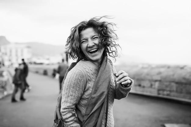 Kręcona kobieta śmieje się stojąc wśród miejskiej ulicy