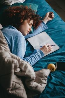 Kręcona kobieta w niebieskiej piżamie zasypiająca po napisaniu pracy domowej w zeszytach