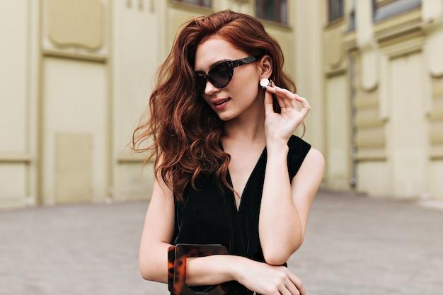Kręcona kobieta w okularach przeciwsłonecznych dotykająca masywnych kolczyków