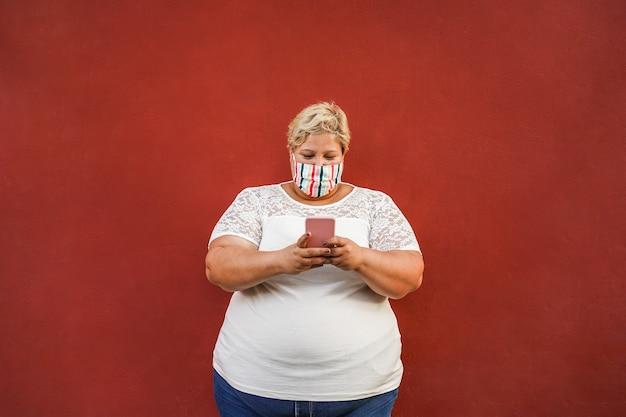 Kręcona kobieta za pomocą smartfona na zewnątrz nosząc maskę ochronną na twarz - koncepcja stylu życia koronawirusa