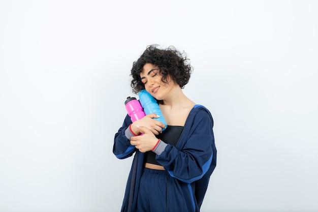 Kręcona krótkowłosa sportowa kobieta przytula różowo-niebieskie butelki z wodą.