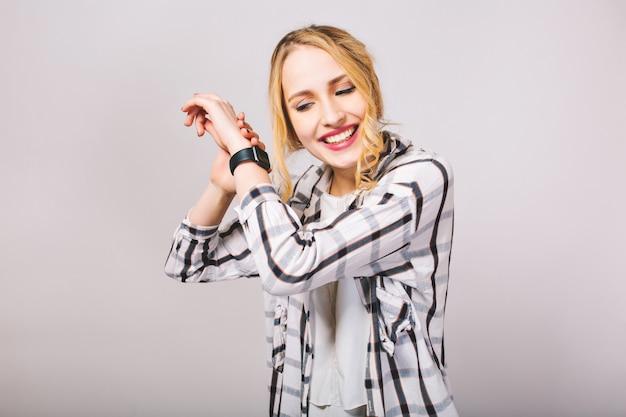 Kręcona ładna dziewczyna w modnej koszuli w paski z zainteresowaniem słucha tykania nowego czarnego zegarka. uśmiechający się atrakcyjna jasnowłosa młoda kobieta pozuje z rękami do góry na białym tle.