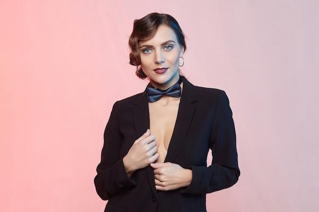 Kręcona młoda kobieta w męskim garniturze i muszce