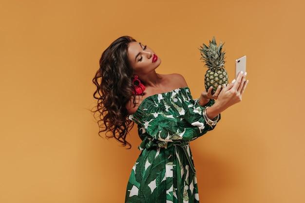 Kręcona, nowoczesna dziewczyna z ciemnymi długimi włosami i dużymi ustami w czerwonych kolczykach i drukowanej letniej sukience robi selfie i trzyma ananasa