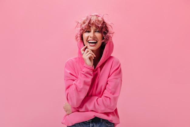 Kręcona różowowłosa kobieta w dobrym nastroju pozuje na izolowanej ścianie
