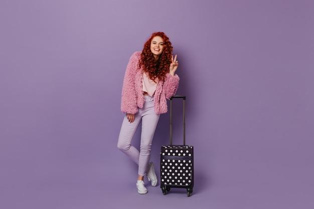 Kręcona rudowłosa kobieta w jasnym wiosennym stroju pokazuje znak pokoju i pozuje z walizką na fioletowej przestrzeni.