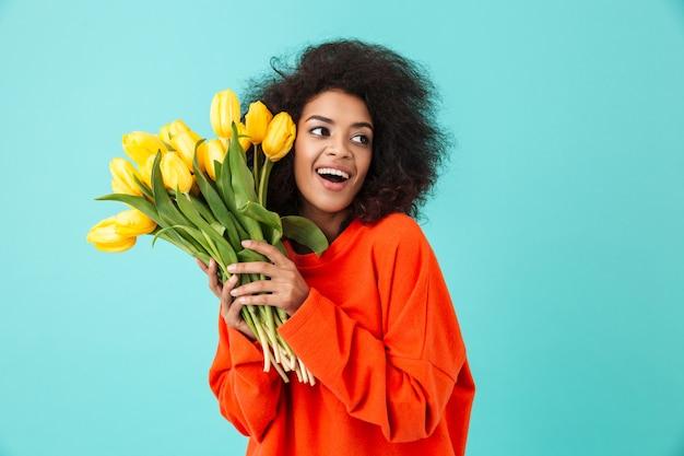 Kręcone amerykańska kobieta w czerwonej odzieży, patrząc na bok i trzymając bukiet pięknych żółtych tulipanów, odizolowane na niebieskiej ścianie