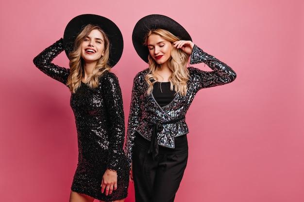 Kręcone brunetka kobieta w błyszczącej sukience przygotowuje się do imprezy z najlepszą przyjaciółką. kryty ujęcie podekscytowanych młodych kobiet w kapeluszach.