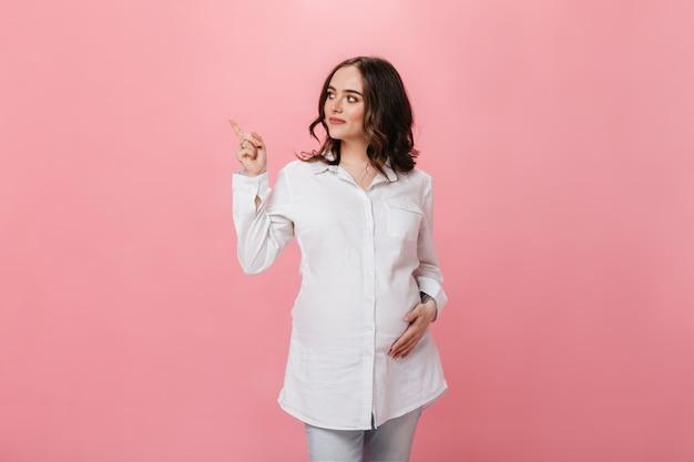 Kręcone brunetka kobieta w ciąży w białej koszuli, wskazując miejsce na tekst na na białym tle. szczęśliwa dziewczyna w dżinsowych spodniach uśmiecha się i pozuje na różowym tle.