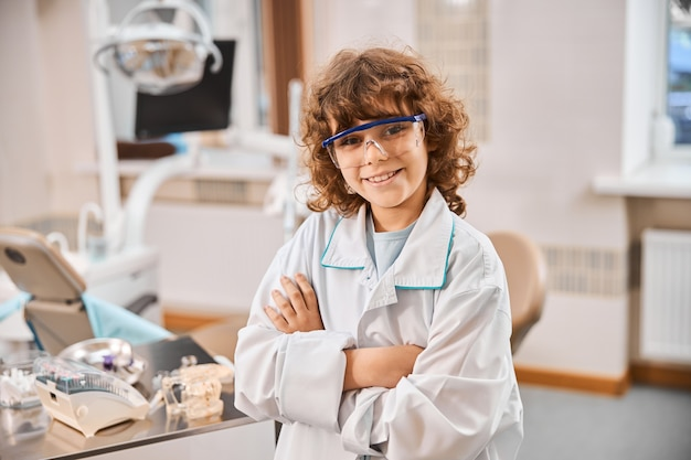 Kręcone brunetki w fartuchu laboratoryjnym i okularach ochronnych stojące ze skrzyżowanymi rękami w gabinecie dentystycznym