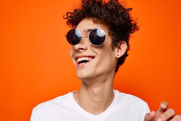 Kręcone facet nosi okulary przeciwsłoneczne moda młodzież styl pomarańczowe tło