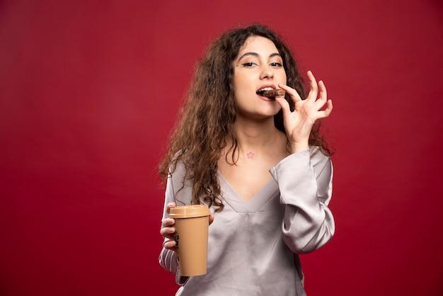 Kręcone kobieta jedzenie czekolady.