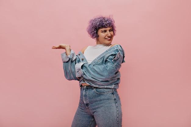 Kręcone kobieta z liliowymi włosami w stylowym garniturze dżinsowym, pozowanie na różowo. zdumiona kobieta odwraca wzrok.