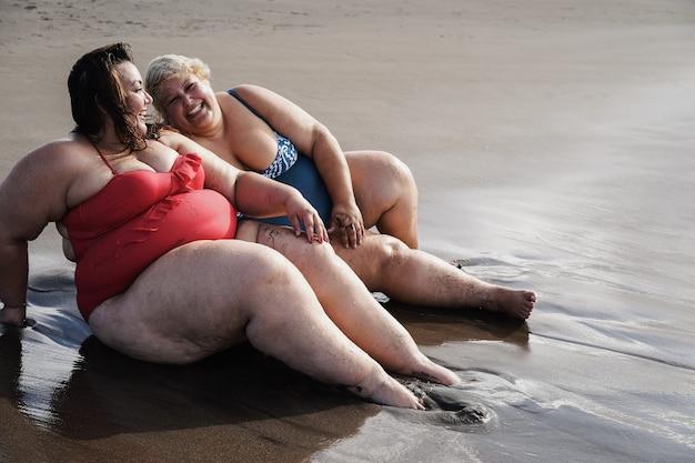 Kręcone kobiety siedzą na plaży, bawiąc się podczas letnich wakacji