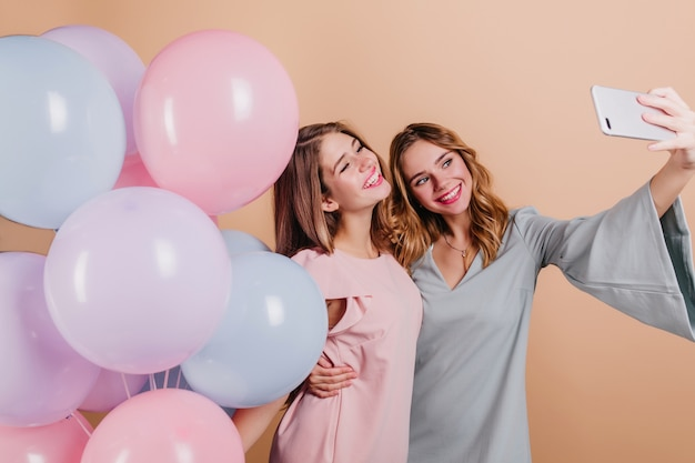 Kręcone kobiety w niebieskiej sukience obejmując siostrę i robiąc selfie