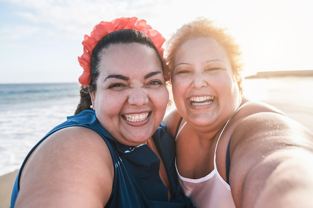 Kręcone koleżanki biorące selfie na plaży z zachodem słońca w tle - szczęśliwa kobieta w rozmiarze plus size, które razem bawią się - krzywe i pewna siebie koncepcja