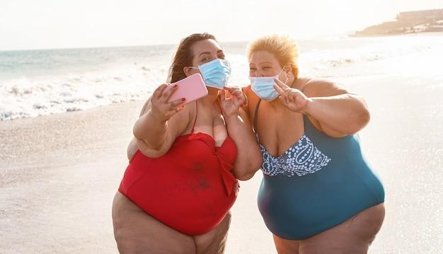 Kręcone koleżanki robiące selfie na plaży z maską na twarz w celu zapobiegania rozprzestrzenianiu się koronawirusa - koncepcja lato i opieka zdrowotna