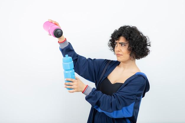 Kręcone krótkie włosy kobieta sportowy z różowymi i niebieskimi butelkami wody stojącej.