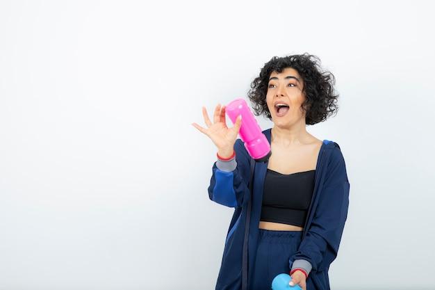 Kręcone krótkie włosy sportowy kobieta trzyma różowe i niebieskie butelki na wodę.