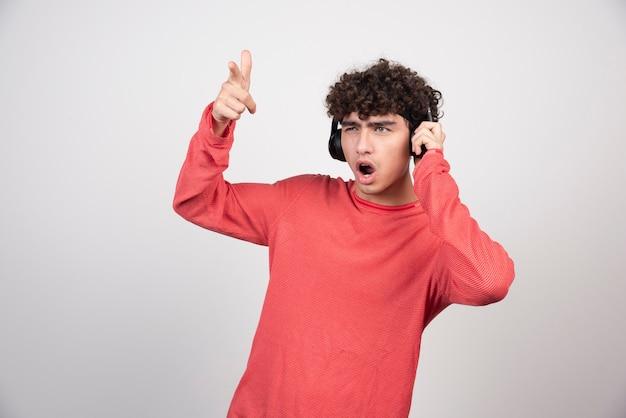 Kręcone młody człowiek słuchając piosenki i śpiewu.