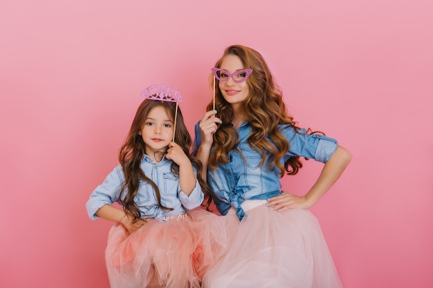 Kręcone piękna dziewczyna z fioletową koroną pozowanie obok młodej atrakcyjnej matki posiadającej maskaradową maskę na różowym tle. urocza kobieta w stroju vintage, zabawy z córką na przyjęciu urodzinowym.