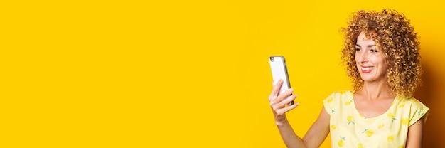 Kręcone szczęśliwa młoda kobieta rozmawia czat wideo przez telefon na żółtym tle. transparent.