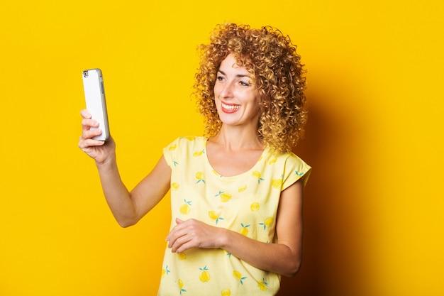 Kręcone uśmiechnięta młoda kobieta rozmawia na czacie wideo przez telefon na żółtym tle.